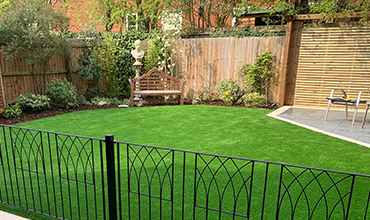 Artificial grass installation with iron wrought decorative fencing in foreground.